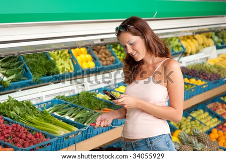 Grocery store - Woman holding mobile phone in a supermarket - stock photo