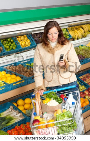 Grocery store - Woman in winter outfit with mobile phone - stock photo