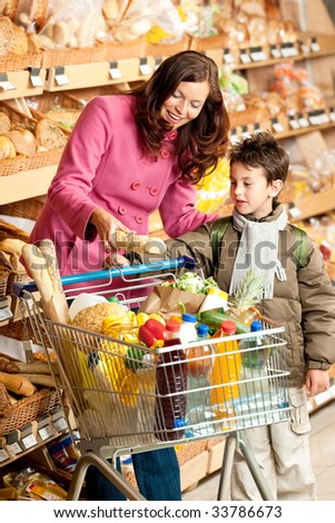 Grocery store - Woman with child buying bread - stock photo