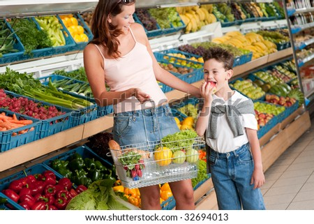 Grocery store - Woman with child  in a supermarket - stock photo