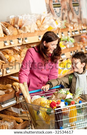 Grocery store - Woman with child in winter outfit in a supermarket - stock photo