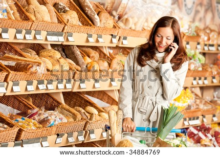 Grocery store: Young brown hair woman with mobile phone and shopping cart - stock photo