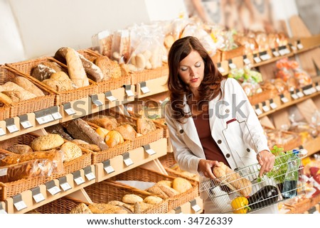 Grocery store: Young woman buying bread at bakery - stock photo