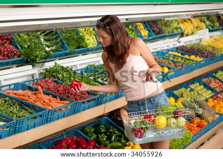 Grocery store - Young woman buying vegetable in grocery store - stock photo