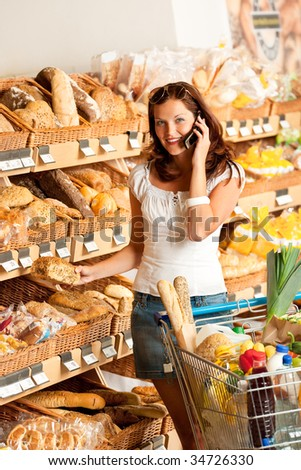 Grocery store: Young woman with mobile phone and shopping cart - stock photo