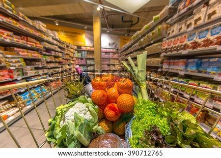 Grocery trolley cart at a supermarket aisle filled up with healthy food products seen from the customers point of view - stock photo