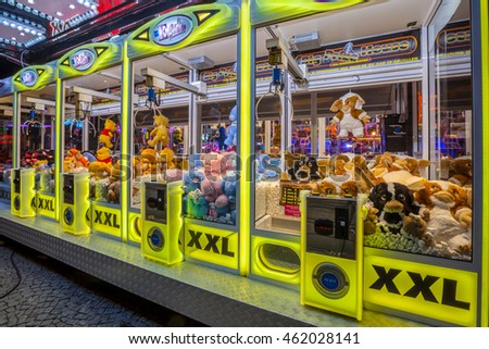 GRONINGEN, THE NETHERLANDS-MAY 5, 2015: Arcade crane vending machine with colourful yellow lights on the annual funfair on central square.