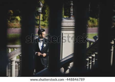 Groom adjusts his black jacket standing on the stone stairs outside