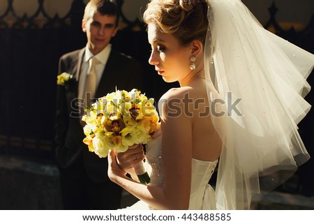 Groom admires a bride standing on the background while she walks in the morning lights