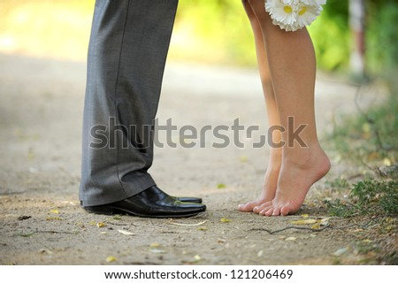 groom and barefooted bride with chamomiles bouquet - stock photo