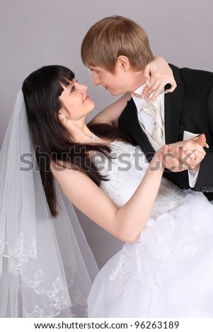 Groom and beautiful bride dance in studio on gray background; close up - stock photo