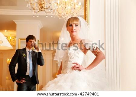 Groom and  bride against a mirror. Groom speaks by phone. - stock photo