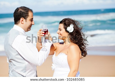 groom and bride drinking  champagne on beach - stock photo
