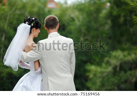 Groom and bride embrace one another in the park - stock photo