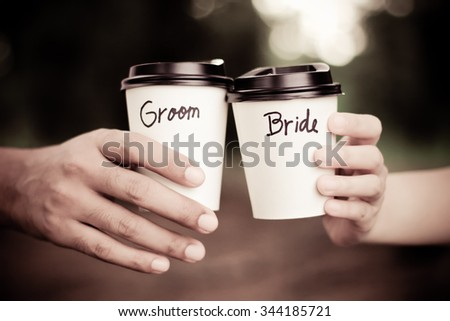 Groom and bride holding coffee cup with retro filter tone - stock photo