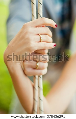Groom and bride holding swing rope