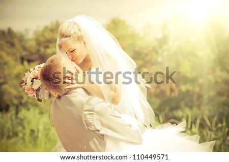 Groom and Bride in a park. wedding dress. Bridal wedding bouquet of flowers - stock photo
