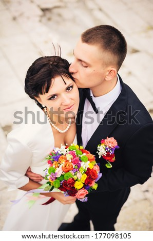 Groom and Bride in a park. Young couple kissing in wedding gown. wedding dress. Bridal wedding bouquet of flowers