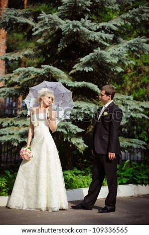 Groom and Bride in wedding dress in a park. Bridal wedding bouquet of flowers