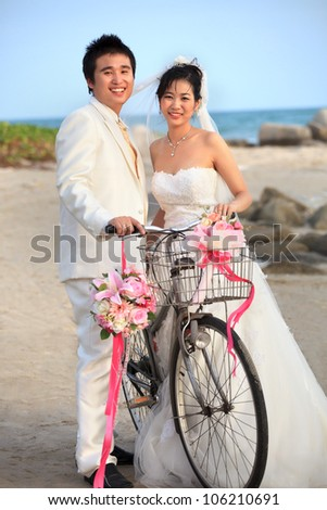 groom and bride in wedding suit standing beside old bicycle - stock photo