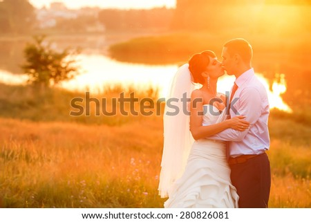 groom  and  bride is hugging and kissing on the background beautiful sunset on the lake
