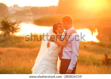 groom  and  bride is hugging on the background beautiful sunset on the lake - stock photo