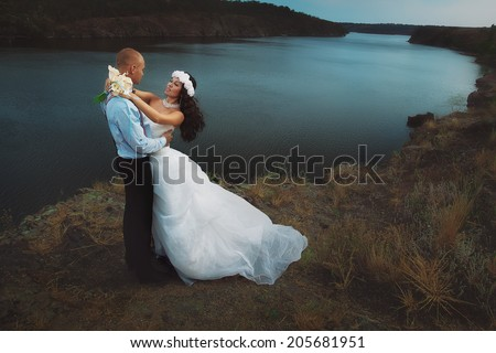 Groom and bride kissing against river - stock photo