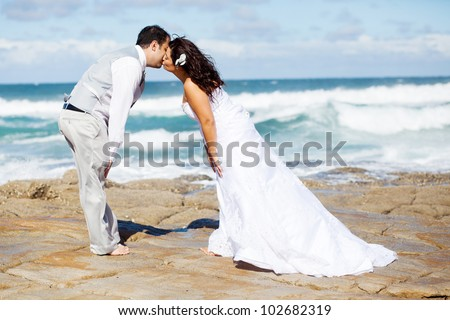 groom and bride kissing on beach - stock photo