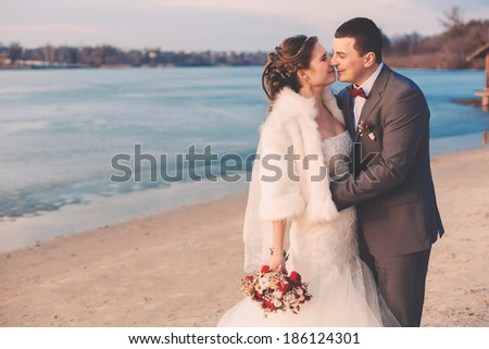 groom and bride laughing on river bank