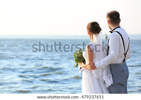Groom and bride on bank of river