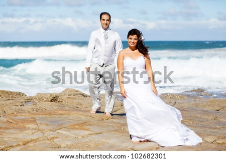 groom and bride on beach rocks - stock photo