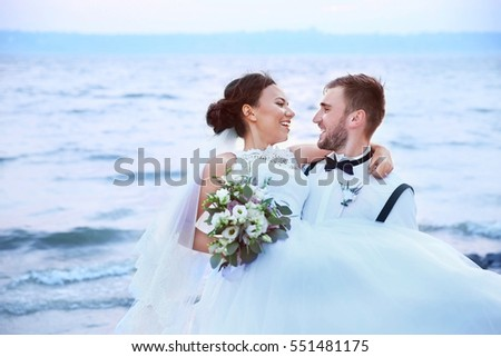Groom and bride on river bank at romantic moment
