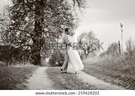 Groom and bride on wedding day. Newlywed couple walking together at countryside.