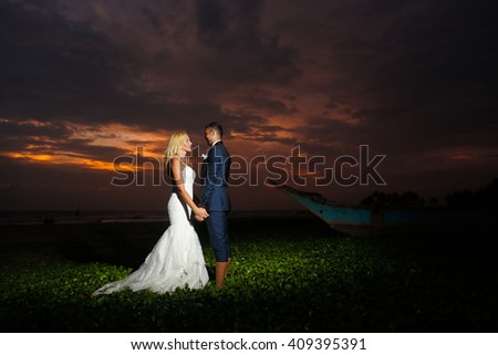 groom and bride posing at sunset on a tropical island - stock photo