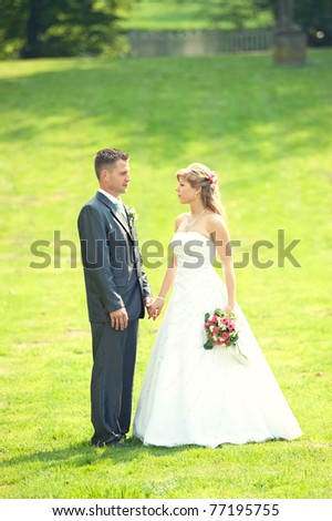 groom and bride posing in a park - stock photo