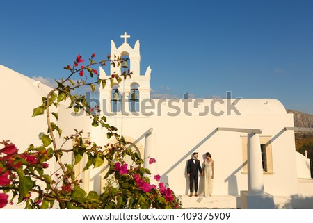 groom and bride posing outside a white church