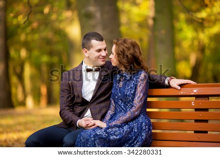 Groom and Bride sitting on bench in a park. smile wedding dress. - stock photo