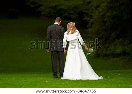 groom and bride walking on grass - stock photo