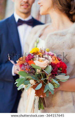 Groom and bride with autumn bouquet