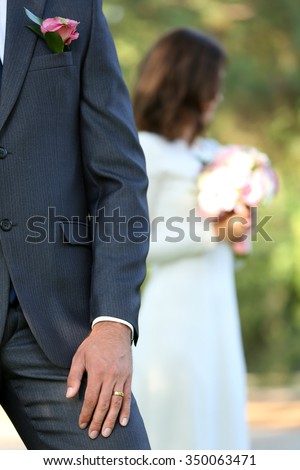 Groom  and bride with wedding bouquet on nature background