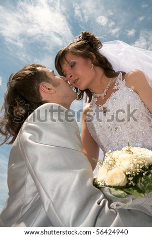 Groom and the bride embrace on a background of the dark blue sky.