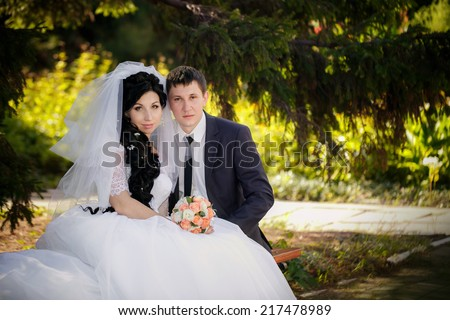 groom and the bride sit on a bench - stock photo