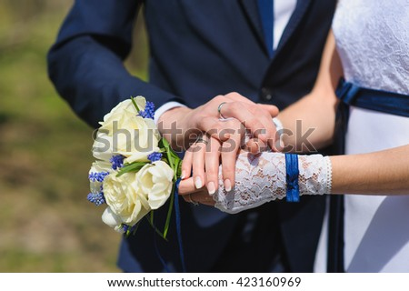 Groom and the bride with a bouquet of roses. Bride with groom holding wedding bouquet at ceremony.  - stock photo