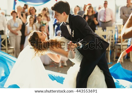 Groom bends bride over during their first dance outside in a sunny day