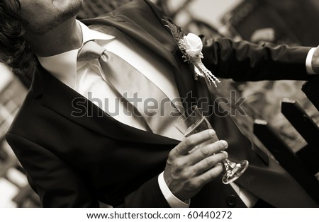 groom - bridegroom is standing there with a glass champagne or sparkling wine - stock photo