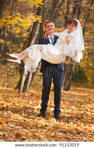 Groom carries bride in his arms - outdoor shot - stock photo