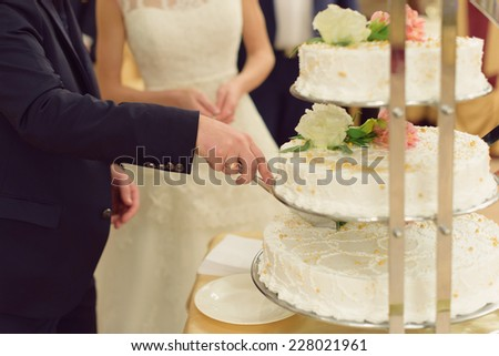 groom cutting white wedding cake - stock photo