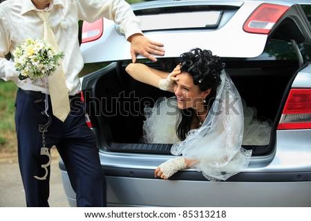 Groom discharging of captive bride from car trunk - stock photo