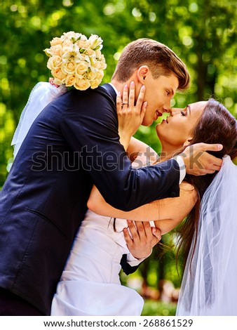 Groom embrace bride outdoor. Man kissing girl.