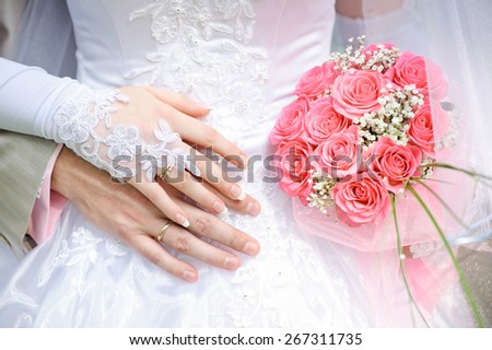 groom embraces the bride, the bride holds a wedding bouquet. - stock photo